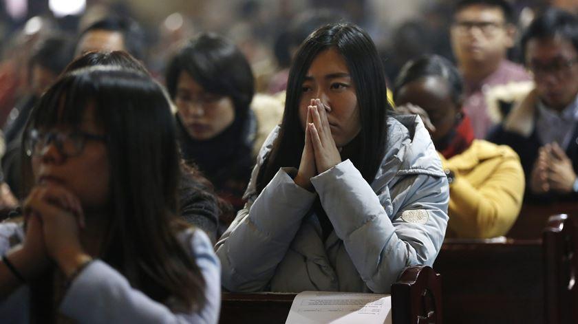 Católicos rezam numa igreja na China. Foto: EPA