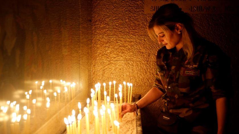 Uma miliciana cristã acende uma vela numa igreja libertada nos arredores de Mossul. Foto: Youssef Badawi/EPA