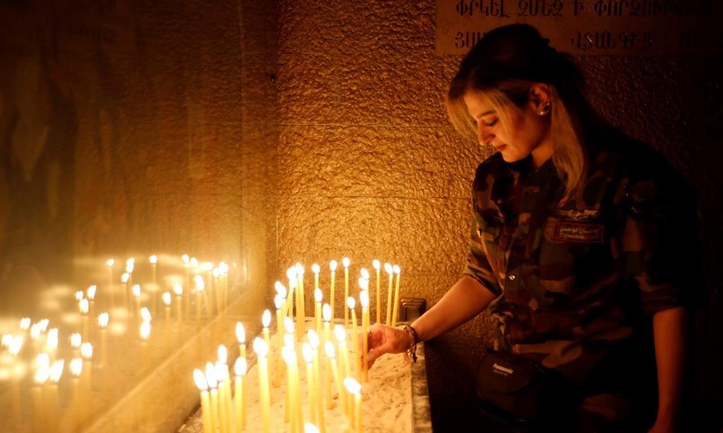 Membro de uma milicia cristã acende uma vela numa igreja, durante a reconquista de Mossul. Foto: Youssef Badawi/EPA